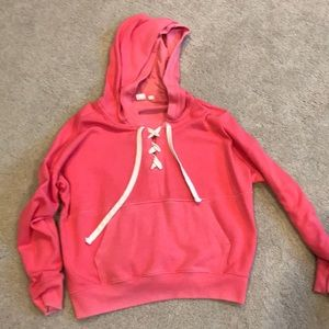 Coral hooded sweatshirt with drawstring.